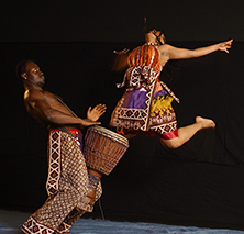 man playing djembe with female jumping in air