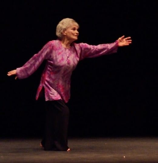 Shirley Ubell on stage reaching out her hand