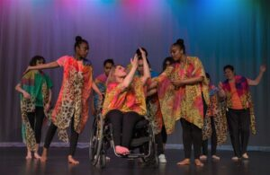 group of girls dancing, women in wheelchair in center with raised hands, group of girls circled around to frame the center